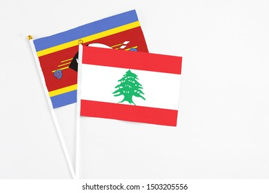 Lebanon and Swaziland stick flags on white background. High quality fabric, miniature national flag. Peaceful global concept.White floor for copy space.