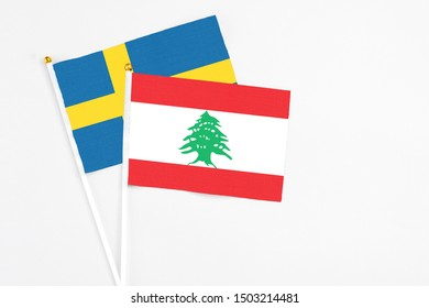 Lebanon and Sweden stick flags on white background. High quality fabric, miniature national flag. Peaceful global concept.White floor for copy space.