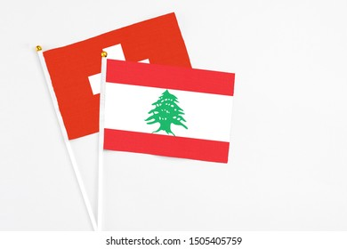 Lebanon and Switzerland stick flags on white background. High quality fabric, miniature national flag. Peaceful global concept.White floor for copy space.