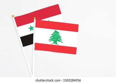 Lebanon and Syria stick flags on white background. High quality fabric, miniature national flag. Peaceful global concept.White floor for copy space.