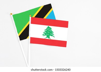 Lebanon and Tanzania stick flags on white background. High quality fabric, miniature national flag. Peaceful global concept.White floor for copy space.