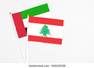 Lebanon and United Arab Emirates stick flags on white background. High quality fabric, miniature national flag. Peaceful global concept.White floor for copy space.