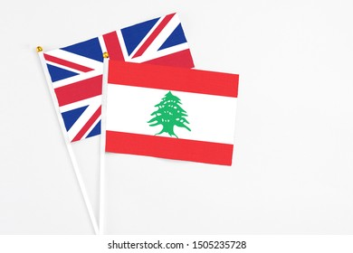 Lebanon and United Kingdom stick flags on white background. High quality fabric, miniature national flag. Peaceful global concept.White floor for copy space.