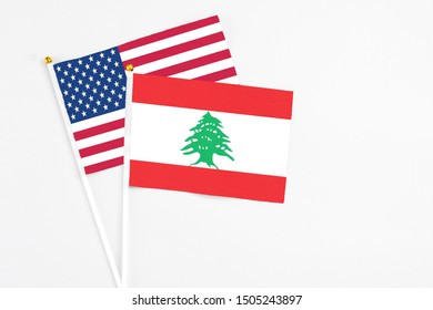 Lebanon and United States stick flags on white background. High quality fabric, miniature national flag. Peaceful global concept.White floor for copy space.