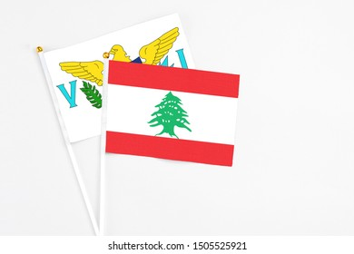 Lebanon and United States Virgin Islands stick flags on white background. High quality fabric, miniature national flag. Peaceful global concept.White floor for copy space.