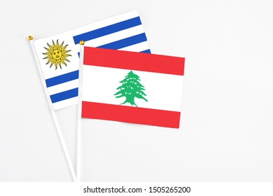 Lebanon and Uruguay stick flags on white background. High quality fabric, miniature national flag. Peaceful global concept.White floor for copy space.