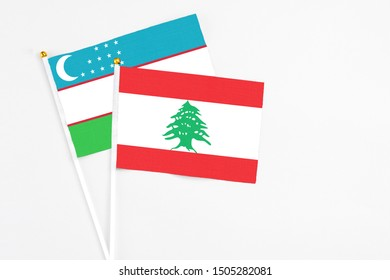 Lebanon and Uzbekistan stick flags on white background. High quality fabric, miniature national flag. Peaceful global concept.White floor for copy space.