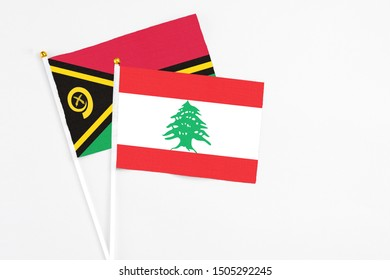Lebanon and Vanuatu stick flags on white background. High quality fabric, miniature national flag. Peaceful global concept.White floor for copy space.