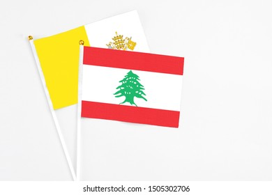 Lebanon and Vatican City stick flags on white background. High quality fabric, miniature national flag. Peaceful global concept.White floor for copy space.