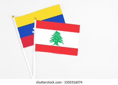 Lebanon and Venezuela stick flags on white background. High quality fabric, miniature national flag. Peaceful global concept.White floor for copy space.