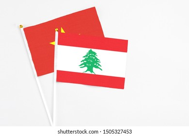 Lebanon and Vietnam stick flags on white background. High quality fabric, miniature national flag. Peaceful global concept.White floor for copy space.