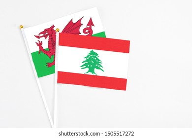 Lebanon and Wales stick flags on white background. High quality fabric, miniature national flag. Peaceful global concept.White floor for copy space.