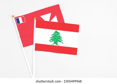 Lebanon and Wallis And Futuna stick flags on white background. High quality fabric, miniature national flag. Peaceful global concept.White floor for copy space.