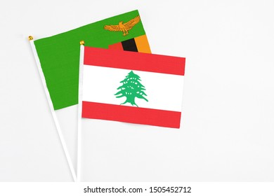 Lebanon and Zambia stick flags on white background. High quality fabric, miniature national flag. Peaceful global concept.White floor for copy space.
