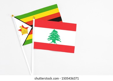 Lebanon and Zimbabwe stick flags on white background. High quality fabric, miniature national flag. Peaceful global concept.White floor for copy space.