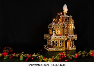 Lebkuchenhaus beleuchtet im Dunkeln mit Verzierungen im weihnachtlichen Stil und schwarzem Hintergrund mit leerem Raum links