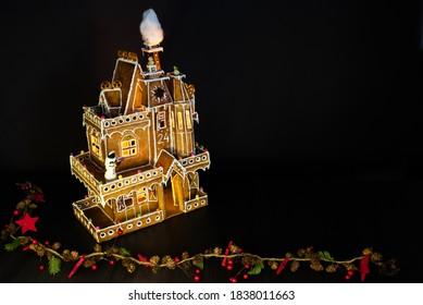 Lebkuchenhaus beleuchtet im Dunkeln mit Verzierungen im weihnachtlichen Stil und schwarzem Hintergrund mit leerem Raum rechts