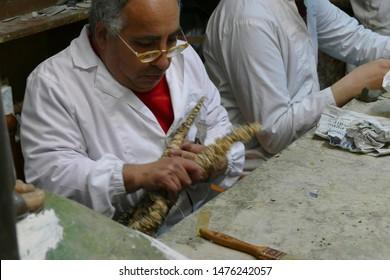 LECCE, ITALY - APR 8, 2019 - Artist working on papier mache statue, Lecce, Puglia, Italy