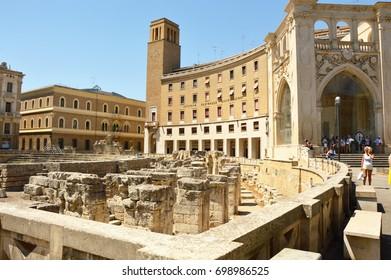 LECCE, ITALY - AUGUST 2, 2017: Roman amphitheater with palaces of the Sedile and the INA (Istituto Nazionale delle Assicurazioni) in Sant'Oronzo square in Lecce, Apulia, Italy