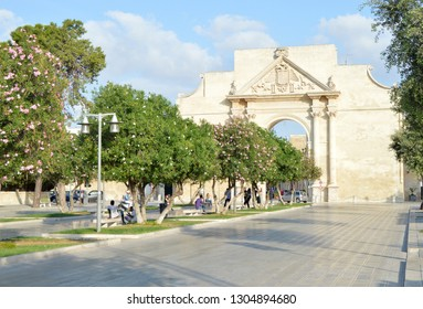Lecce, Italy. The Flowers of oleander and the Triumphal arch well, known as Neopolitan gate or Porta Napoli in Lecce. Puglia was erected in 1548 in Honor Charles 5.