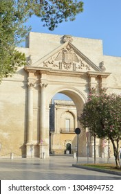 Lecce, Italy. the flowers of oleander and the Triumphal arch, commonly known as Neopolitan gate or Porta Napoli in Lecce. Puglia was erected in 1548 in honir Charles 5.