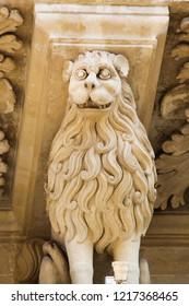 Lecce, Italy - March 13, 2015: Lion statue at the Basilica of Santa Croce, a famous baroque church in Lecce, Apulia, Southern Italy.