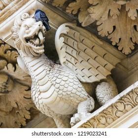 Lecce, Italy - March 13, 2015: Dragon statue at the Basilica of Santa Croce, famous baroque church in Lecce, historic city in Apulia, Southern Italy.