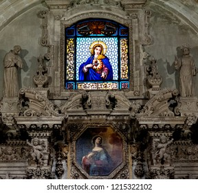 Lecce, Italy, October 2018: a stained glass window of the Virgin Mary and  decorative stone carvings adorn the interior of one of Lecce many baroque churches in Puglia, southern Italy .