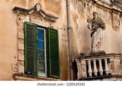 Lecce, Italy, October 2018: a stone baroque statue on a balcony overlooking the entrance to the popular Piazza del Duomo square in the historic centre of Lecce, Puglia, southern Italy.