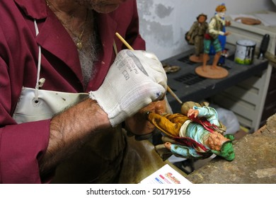 Lecce, Italy - September 15, 2015: An artist puts the finishing touches on a figurine at La Cartapesta in Lecce. The city is renowned for the centuries-old art of papier-mâché.
