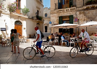 Lecce, Puglia, Italy, October 2018: two tourists on bicycles exploring the streets and squares of the popular Baroque city of Lecce in Italy's southern region of Puglia.