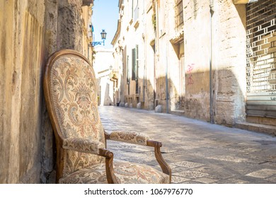 Lecce town, Italy. Vintage chair with old town street in background.