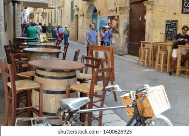 Lecce,Italy.The middle of September 2017.The cityscape of old Lecce with one of the numerous sidewalk cafe with tables as a wine cask.