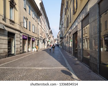 LECCO, ITALY - FEBRUARY 20, 2019: people walk on street via Camillo Benso Conte di Cavour in Lecco city. Lecco is city in Lombardy, the capital of the province of Lecco