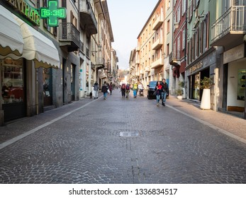 LECCO, ITALY - FEBRUARY 20, 2019: tourists walk on street via Camillo Benso Conte di Cavour in Lecco city in evening. Lecco is city in Lombardy, the capital of the province of Lecco