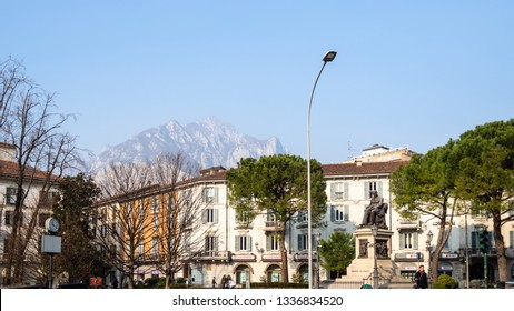 LECCO, ITALY - FEBRUARY 20, 2019: people on square piazza Manzoni with Monument Alessandro Manzoni in Lecco city in evening. Lecco is city in Lombardy, the capital of the province of Lecco