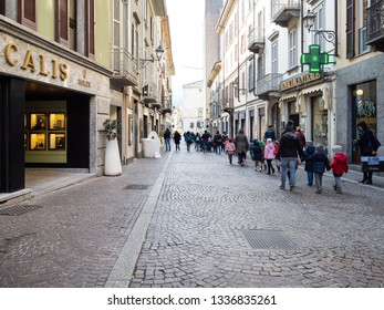 LECCO, ITALY - FEBRUARY 20, 2019: children and tourists walk along shops on street via Camillo Benso Conte di Cavour in Lecco city. Lecco is city in Lombardy, the capital of the province of Lecco