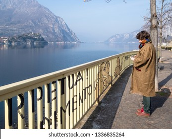 LECCO, ITALY - FEBRUARY 20, 2019: tourist looks into the mobile phone on waterfront Como Lake along street via Adda in Lecco. Lecco is city in Lombardy, the capital of the province of Lecco