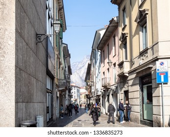 LECCO, ITALY - FEBRUARY 20, 2019: people walk on street Via Roma in Lecco city and view of San Martino mount through the street. Lecco is city in Lombardy, the capital of the province of Lecco