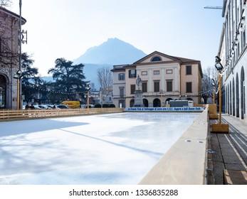 LECCO, ITALY - FEBRUARY 20, 2019: empty ice-skating rink in front of Teatro della Societa (Theatre of Society) on square Piazza Giuseppe Garibaldi in Lecco city in sunny winter day.