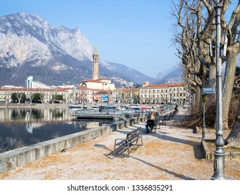 LECCO, ITALY - FEBRUARY 20, 2019: tourist on a bench on the waterfront Riva Martiri delle Foibe of Lario Como Lake in Lecco city. Lecco is city in Lombardy, the capital of the province of Lecco