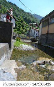 Lecco/Italy - August 1, 2013: Two boys are fishing in the mountain stream with fishing rod.