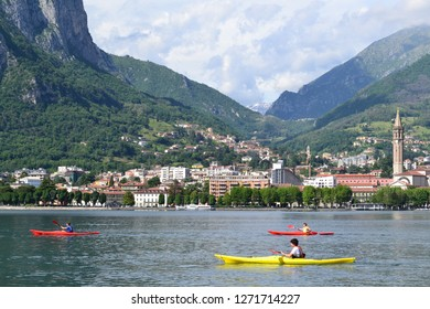 Lecco/Italy - June 6, 2013: Beautiful panoramic view to the Lecco lakefront in a summer sunny day and canoas workout on the lake of Lecco.