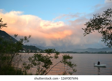Lecco/Italy - May 7, 2014: Exciting panoramic view to a purple stormy cloudscape over the Lecco mountains on the blue sky and a fisher sitting in a motorboat at the lake Pusiano near Lecco.