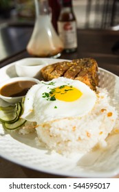 lechon kawali with garlic rice and egg on top