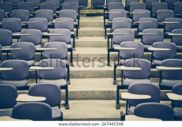 Sillas de clase en una habitación con escalera en medio de una clase