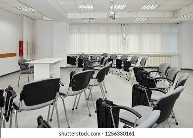 Lecture hall with seats for people. On the stage desks for teachers speaker
