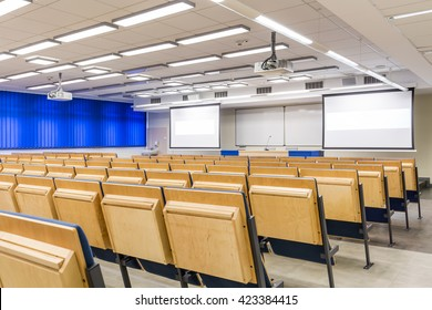 Lecture hall with shaded windows and projection screens