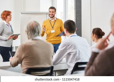 Lecturer with group of people in discussion at business training seminar