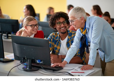 lecturer with group of smiling students working in computer class on university campus